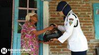 Seorang Satpam menyerahkan paket sembako kepada warga terdampak pandemi Covid-19. (Foto: Istimewa)