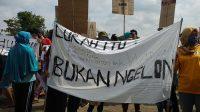 Warga Adimulyo membentangkan spanduk saat aksi unjukrasa. (Foto: Istimewa)