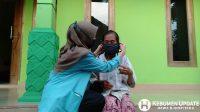 Mahasiswa KKN membantu memakaikan masker kepada warga. (Foto: Istimewa)